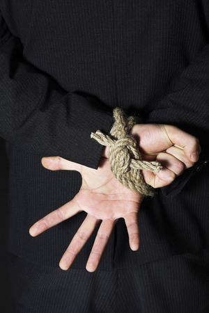 Businessman with his hands tied to the back photo