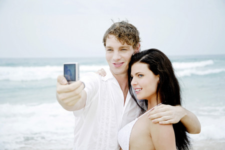 Couple taking picture on together on the beach photo