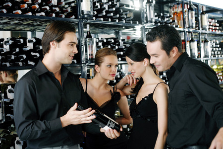 Men and women choosing wine in a wine cellar photo