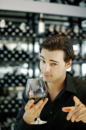 Man pointing at the camera while enjoying a glass of wine photo
