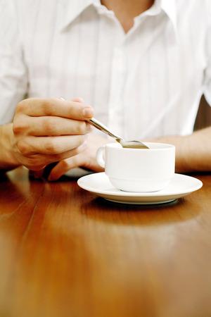 stirring: Man stirring a cup of coffee