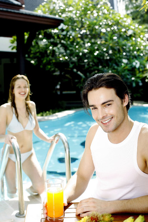 Man holding a glass of orange juice while his girlfriend climbing up from the swimming pool photo