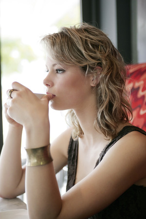 spaghetti strap: A teenage girl sipping hot tea carefully while looking out of the cafe