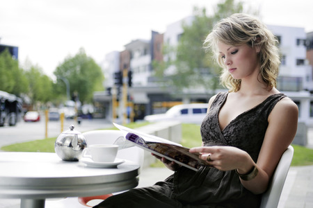 A teenage girl reading a magazine at an open air cafe while waiting for her friend photo