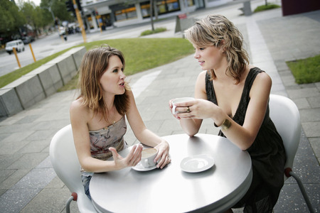 Two friends chit chatting in an open air cafe