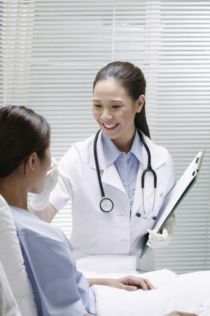 Female doctor taking her patients temperature