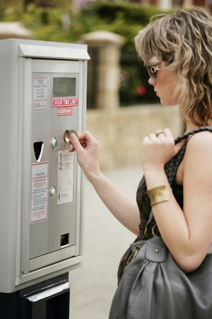 area sexy: A teenage girl inserting coin into the parking meter
