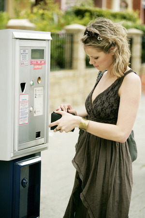 area sexy: A teenage girl searching for coin for parking meter Stock Photo