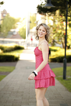 spaghetti strap: A teenage girl in pink dress spending time leisurely in a park
