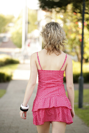 spaghetti strap: Rear view of a teenage girl in pink dress