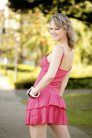 A teenage girl in pink dress posing for a photo shoot in the park