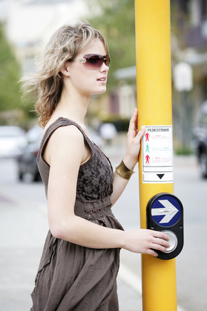 spaghetti strap: A teenage girl pressing the traffic light button for pedestrian passing
