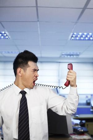 Businessman shouting into a telephone receiver photo