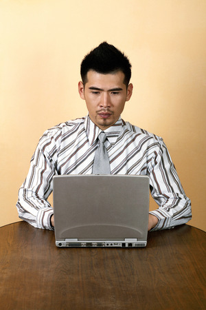 Businessman sitting at the table using laptop photo