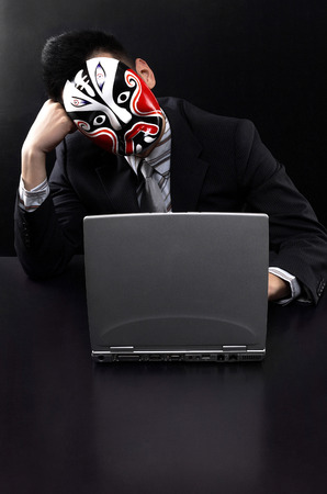 Businessman with oriental mask using laptop photo