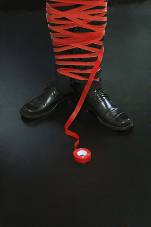 Businessman tied up in red tape photo