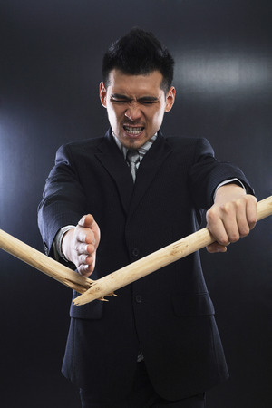 Businessman chopping stick with his bare hand photo