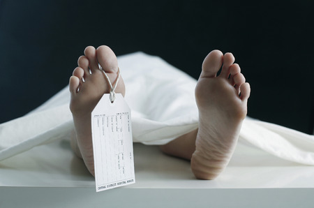 Toe tag hanging on woman lying on table in morgue 写真素材