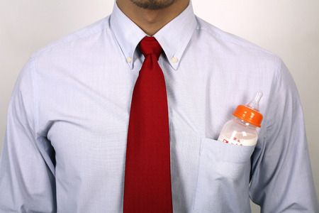 Businessman with baby bottle in his shirt pocket photo