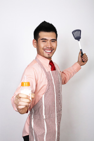 Businessman in apron holding baby bottle and ladle photo