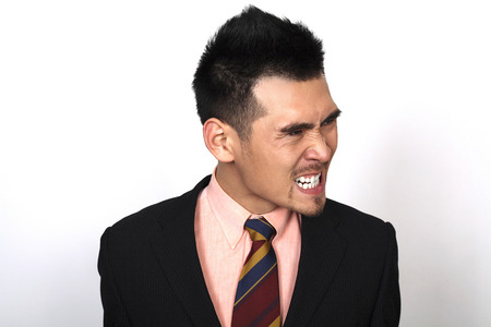 clenching: Angry businessman clenching teeth