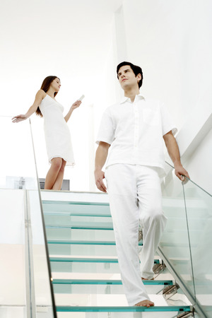 Woman text messaging on the phone while her boyfriend is walking down the stairs photo