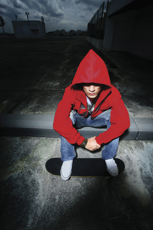 Man in red hooded sweater sitting on sidewalk, stepping on skateboard photo