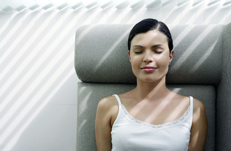 Woman lying on the couch with her eyes closed photo