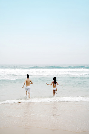 Couple running to the sea photo