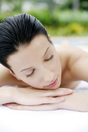 massage table: Woman lying forward on massage table with her eyes closed