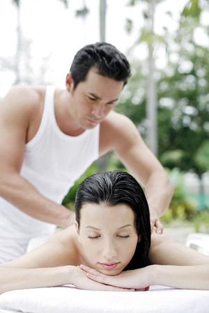 masaje corporal: Mujer recibiendo un masaje de cuerpo en el lado de la piscina