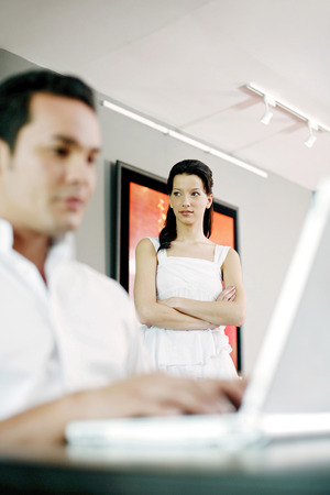 Man using laptop with his girlfriend standing in the background photo