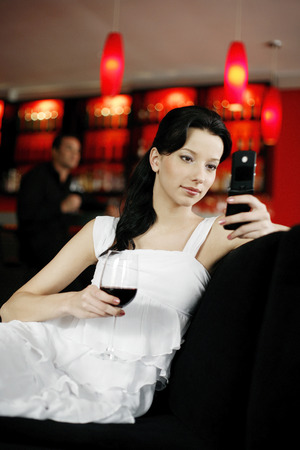 view of an elegant red couch: Woman text messaging on the mobile phone while holding a glass of wine