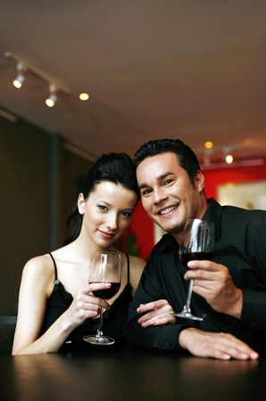 Couple with wine glasses posing for the camera photo