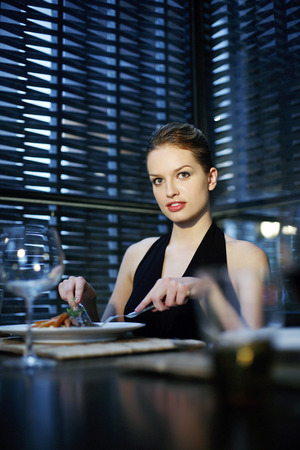 Woman enjoying her meal in a luxurious restaurant photo