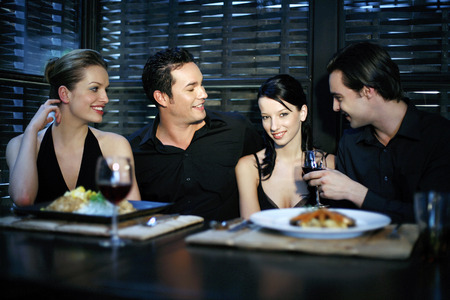 Men and women chatting while having dinner in a restaurant photo