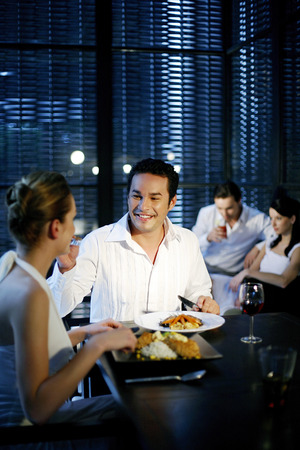 Man feeding his girlfriend while having dinner in a restaurant photo