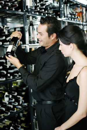 Couple choosing wine in a wine cellar photo