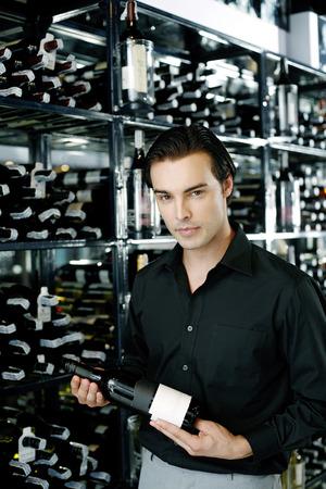 Man choosing wine in a wine cellar photo