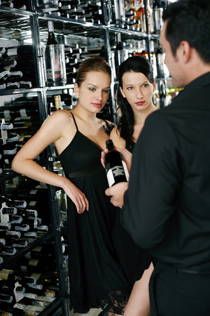 Man recommending a bottle of wine to two beautiful women photo