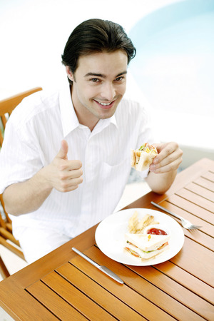 Man showing thumbs up while enjoying his breakfast photo