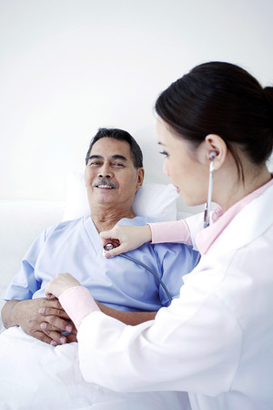 professionalism: Doctor examining patient in a ward Stock Photo
