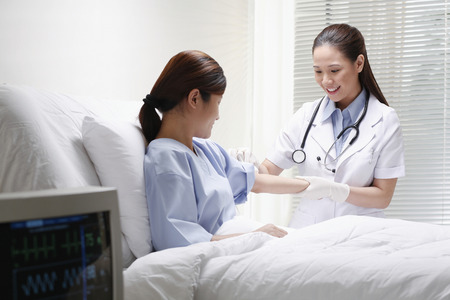 Female doctor cleaning her patient's arm before an injection Banque d'images