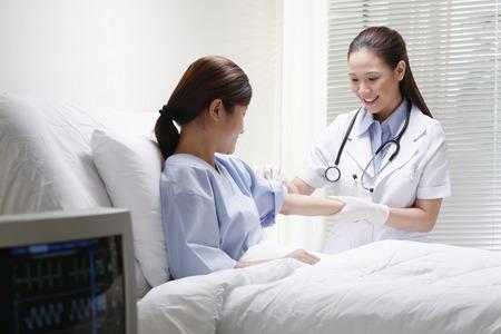 Kobieta lekarz czyszczenia ramieniu pacjenta przed zastrzykiem