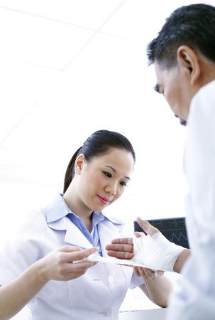 carefully: Nurse bandaging a patients hand
