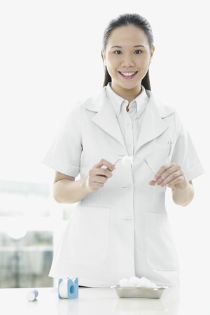 cotton swab: Female doctor picking up cotton swab with forceps Stock Photo