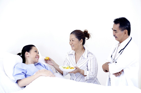 Mother feeding sick daughter in hospital, doctor standing beside photo