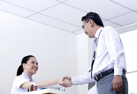 thanking: Two adults shaking hands Stock Photo