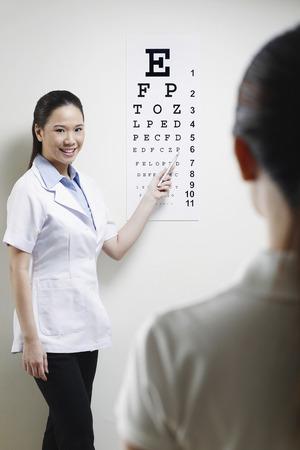 doctora: Mujeres m�dico probar la vista de su paciente