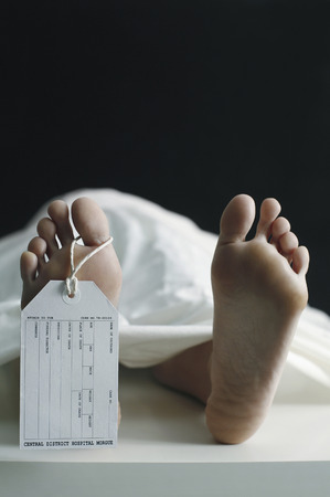 Toe tag hanging on woman lying on table in morgue Stock Photo